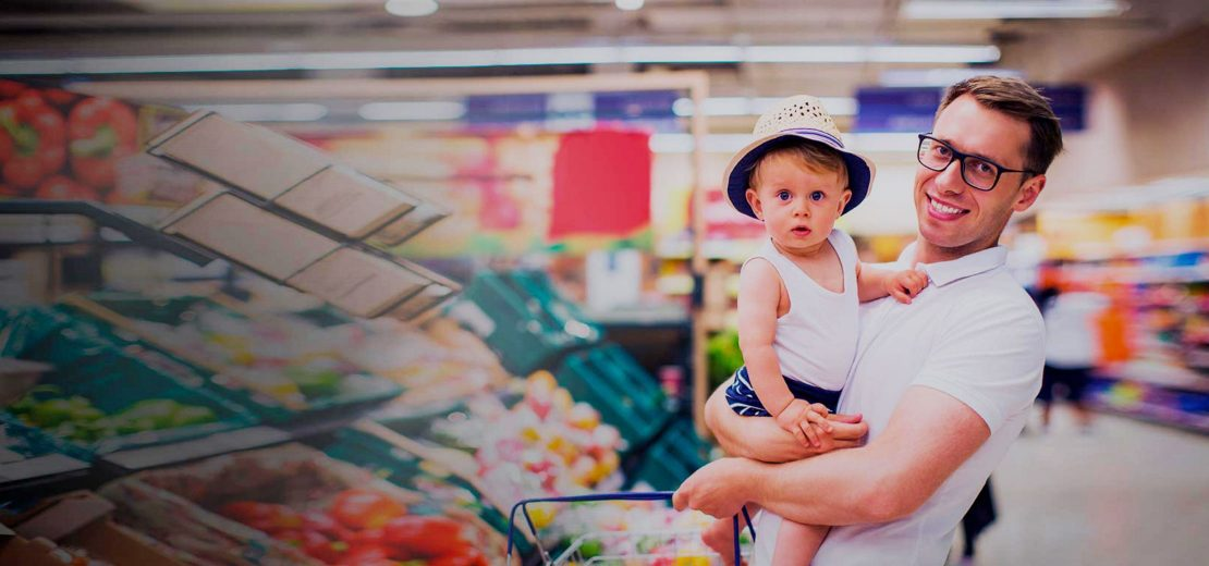 man holding a child in a supermarket in the vegetables section
