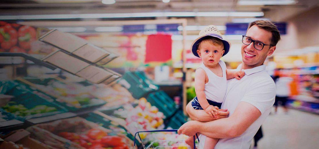 homme portant un enfant au supermarché rayon légumes