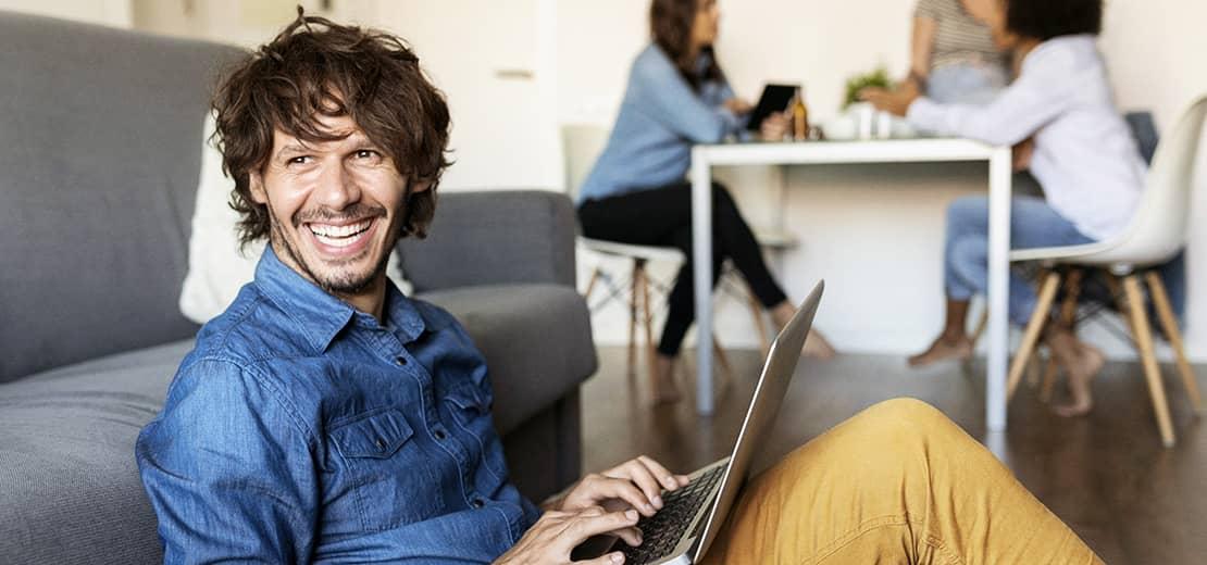 homme souriant assis avec un ordinateur sur les genoux