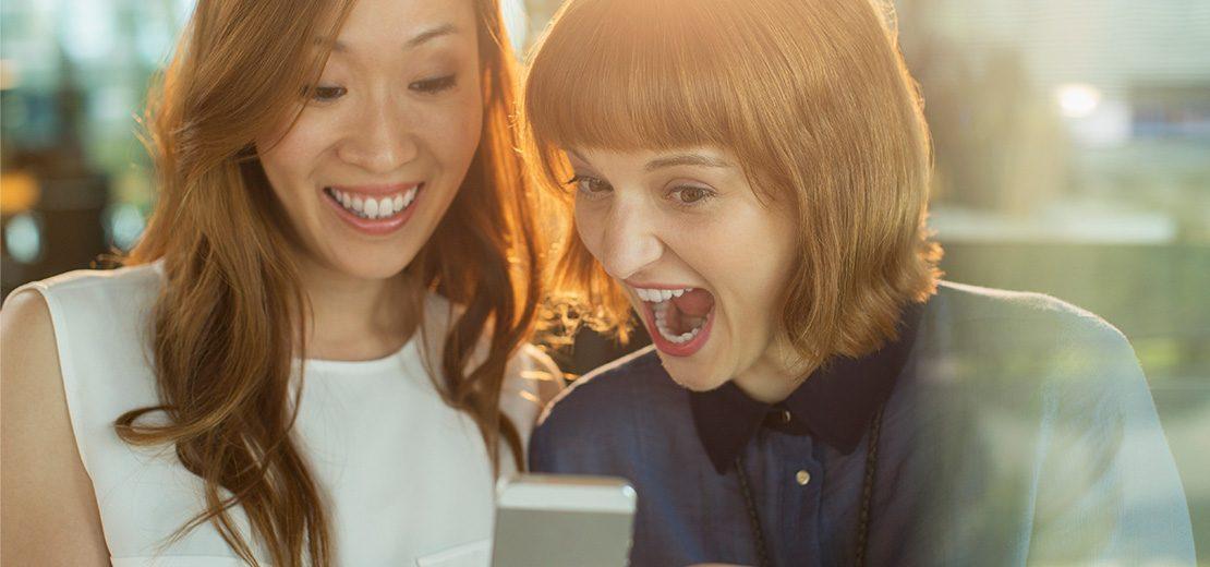 deux femmes s'amusent en regardant un smartphone